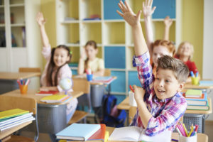 Portrait of cute boy raising hand at workplace with his classmates behind
